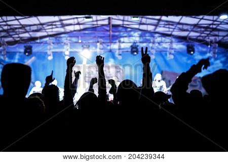 silhouettes of concert crowd in front of bright stage lights, cold colors