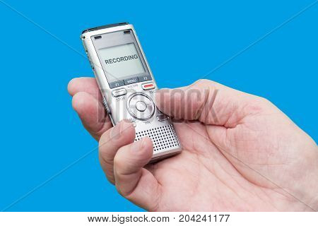 Elderly man is holding voice recorder on blue background color and contrast manipulated