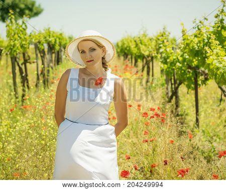 Woman in a hat with poppy flower on a grape field. Portrait of a beautiful woman in grape field.