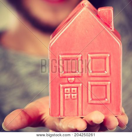 Household savings housekeeping concept. Man holding tiny red statue in shape of house. Studio shot on blue background