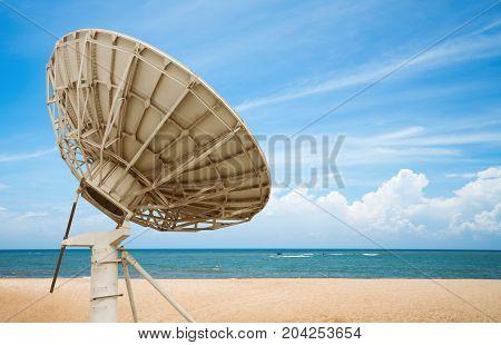Blue ocean and soft sandy beach satellite antenna close-up.