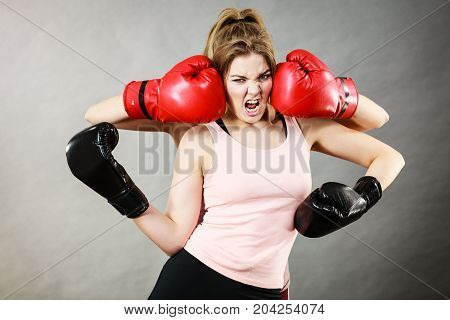 Sporty having head between boxing gloves somebody punching her. Studio shot on grey background.