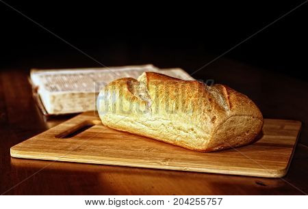 A rustic loaf of bread is on a wood cutting board in front of an open Holy Bible in the background. Bread is powerful symbol for the Christian faith (i.e., daily bread and bread of life).
