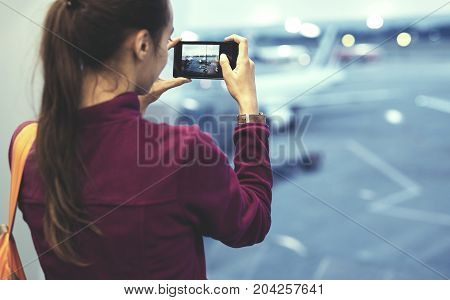 Girl at the airport window looking outside and photographing a plane