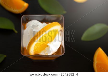 Orange Jelly In A Cup With Whipped Cream And Orange Sliced On Black Wooden Background