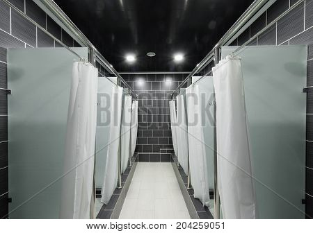 public shower room with curtains in the booths