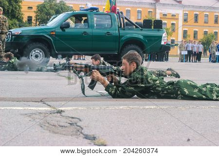 Zhytomyr, Ukraine - May 03, 2015: happy teen boy shooting on a stump at military competition