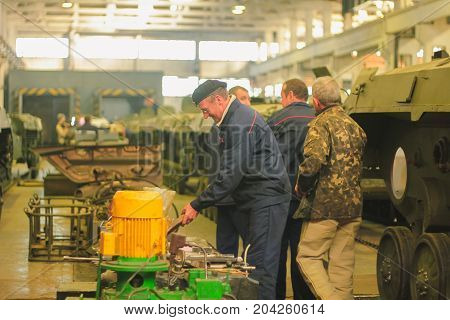 ZHYTOMYR, UKRAINE - Oct 10, 2014: Russian armored personnel carrier with a weapon and tanks in the hangar
