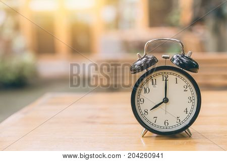 Clock On Wood Table With Green Nature Background Time At 8 O'clock Morning