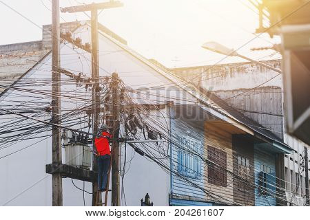 cable technician ladder up to fix messy cable line in electricity pole in Thailand