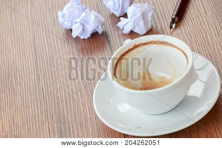 Empty cup of coffee with wrinkle put on old wooden tabletop