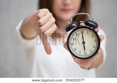 Asian Business Woman Show Thumbs Down With A Clock Time At 6 O'clock For Bad Time Unlike Delayed Fin