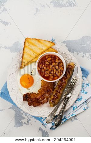Traditional english breakfast with fried eggs, bacon, sausages, toasts and beans over white stone table. Space for text. Selective focus