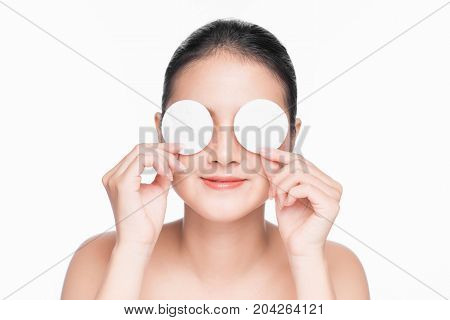 Young asian girl cares for face skin relaxation using cotton pad.
