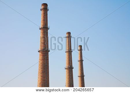 Smokestacks made of bricks against the sky