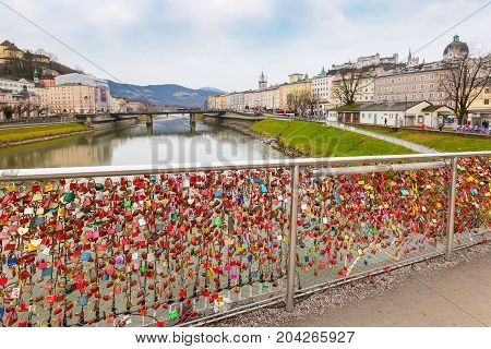 Salzburg, Austria - December 25, 2016: Historic city of Salzburg with love padlocks bridge and Hohensalzburg Festung castle across Salzach river, Austria