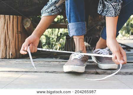 Close up girl hands tying shoelace on shoes after walking