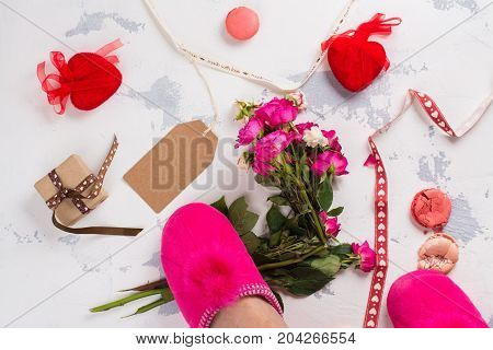 I hate Valentines day concept. After party mess with flowers, gift box, cookies and decorative hearts. Top view. Space for text
