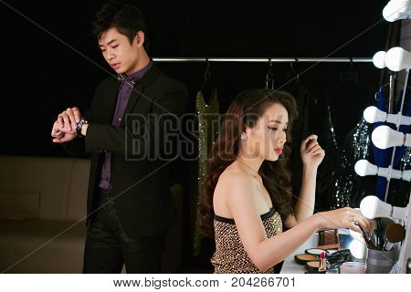 Vietnamese young man waiting when his girlfriend applying make-up in front of mirror