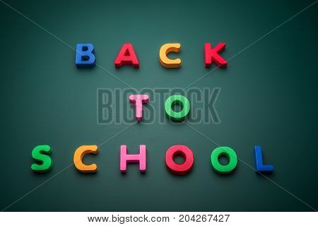 Back to school text write with wooden alphabet in blackboard.
