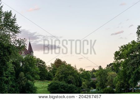 castle tower can be seen through trees in blue hour evening