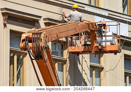 Construction worker works on a crane in summer