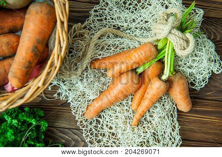 Top View Bunch Of Fresh Organic Dirty Carrots And Oher Purchased Products From Farm Market On The Wo