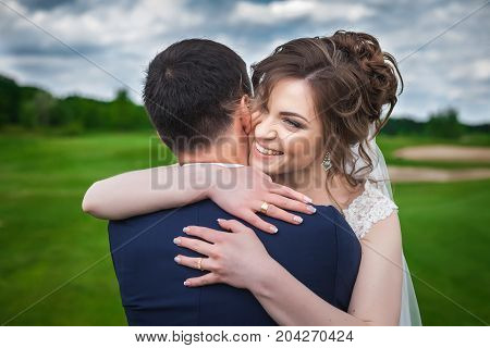 portrait of beautiful bride and stylish asian groom. Woman in wedding white dress and man in dark blue suit. Hugging and smiling