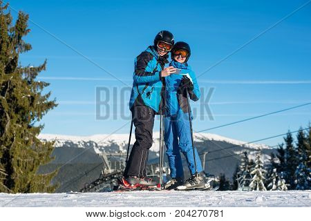 Couple Skiers Standing On Mountain Top Together At A Winter Resort With Ski Lift And Blue Sky In Bac