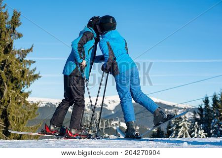 Couple Skiers Kissing On Mountain Top With Mountain And Blue Sky In Background. Dressed At Blue Warm