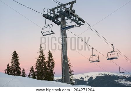 Ski lift chairs on winter resort against a beautiful sky at sunset. Carpathian Mountains Bukovel Ukraine