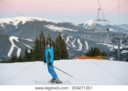 Girl Makes Ski Mountaineering. Woman At Ski Resort Wearing Helmet, Blue Ski Suit And Goggles. Carpat