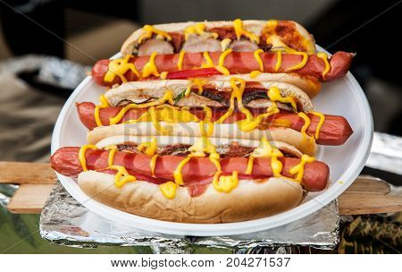 Three Hot Dogs With Ketchup And Mustard In A White Plate