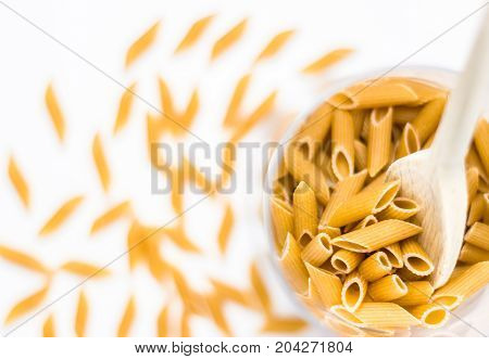 Close up of whole pasta in a glass bowl and wooden spoon on white background. Top view. Shallow depth of field.