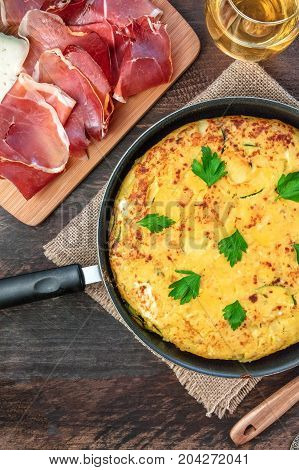An overhead photo of a Spanish tortilla with potatoes and zucchinis, shot from above on a dark rustic texture in a tortillera, with slices of jamon, and a glass of white wine, with a place for text
