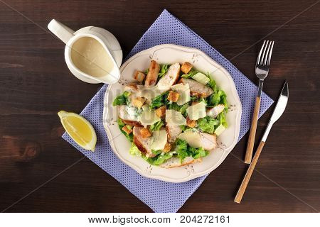 An overhead photo of a plate of chicken Caesar salad on a dark rustic background with a gravy boat, a slice of lemon, a fork and a knife, and copy space