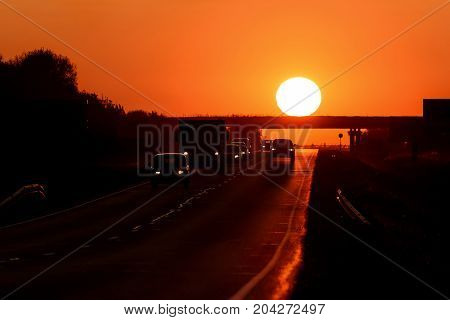Colorful abstract background with an asphalt road cars and a round sun over a bridge against the background of a fiery red-orange sky at sunset