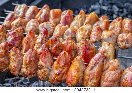 Crispy golden brown pork knuckles on a grill, outdoors barbecue