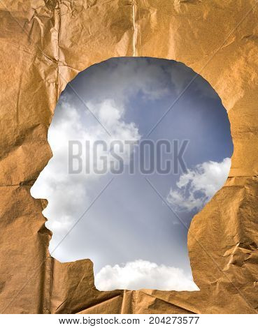 Crumpled paper shaped as a human head. Cloudy sky inside the head. Dream and imagination concept.