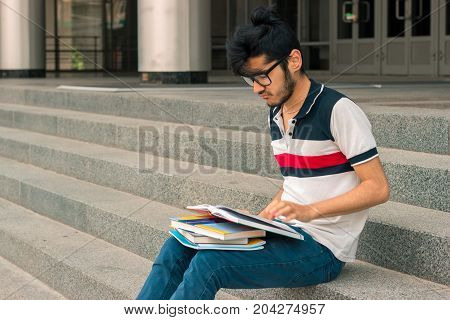 young charming guy with black hair is sitting on the stairs and reads books