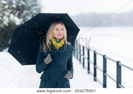 Woman with long blond hair on white snow landscape. Christmas and new year. Model smiling in grey coat scarf and mittens. Holidays celebration concept. Girl walking with umbrella on winter day.