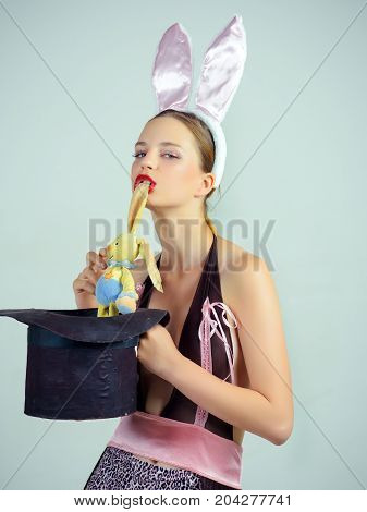 Hat trick concept. Magician pulling rabbit toy out of top hat. Magic and entertainment. Woman wearing bunny ears. Girl in  lingerie on grey background.
