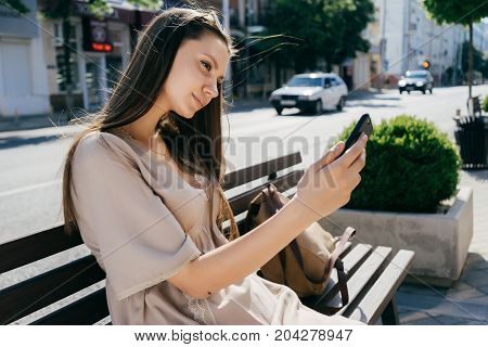 Beautiful glamorous girl doing selfie on the street sitting on the bench.