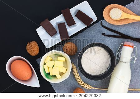 Food concept Bakery preparation by flour, egg, butter, sugar, chocolate, vanilla beans, walnuts and milk decor by wheat ear on bake paper and black background