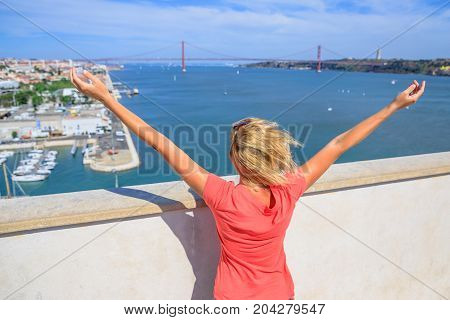Bridge of 25 April and Tagus or Tejo river from Discoveries Monument. Happy tourist woman with open arms at Padrao dos Descobrimentos platform. Belem District, Lisbon, Portugal. Europe travel concept.