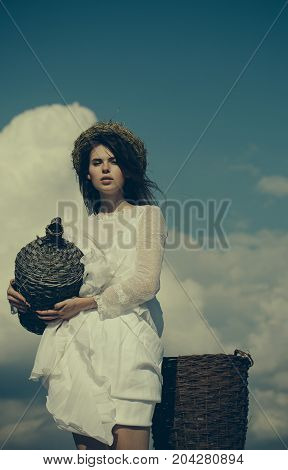 Girl with wicker bottle and harvest basket. Woman in white dress and wreath on cloudy sky. Harvesting and winemaking. Summer vacation holidays and celebration. Winery tour concept.