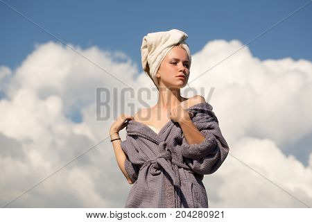 Model sunbathing on sunny day. Spa and wellness. Summer vacation concept. Woman in bathrobe and towel on head. Girl posing with naked shoulders on cloudy blue sky.