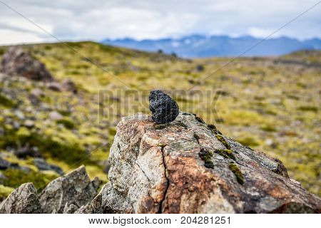 A lava stone standing against the backdrop of Icelandic landscapes and vegetation.