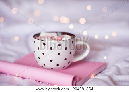 Sweet cup of coffee staying on pink notebook in bed over Christmas lights closeup. Good morning. Selective focus.