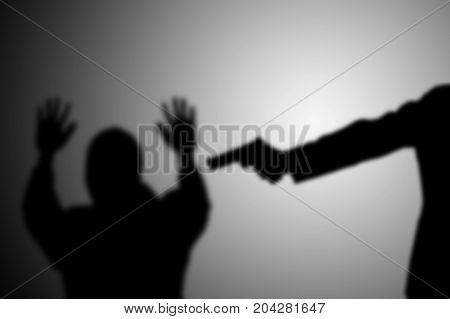 Man with gun point to victim's head. black and white. robbery, murder, crime and security concept.